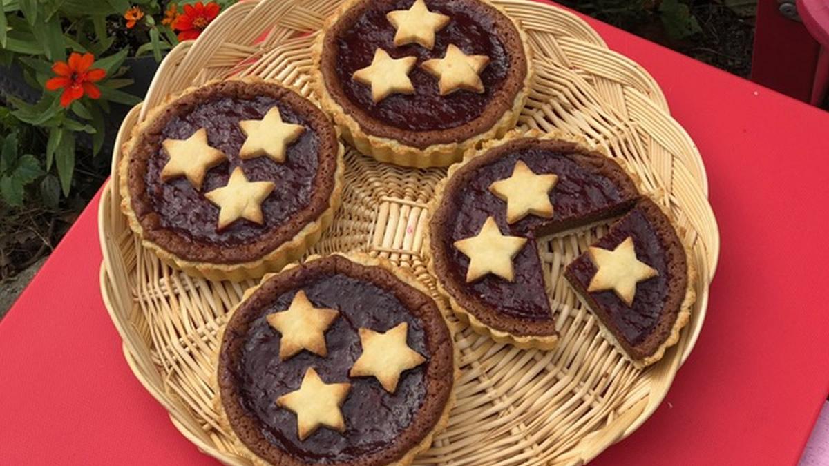 Strawberry Rose Jam glazed gluten-free cheesecake tartlets arranged on a straw plate | AnnaMaria's