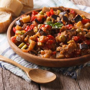 Ready to eat caponata on a wooden plate with spoon | AnnaMaria's